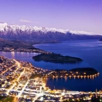 Night time over Queenstown, New Zealand with city lights below. Lake Wakatipu and the Snow Capped Remarkables mountain range. Just after sunset.